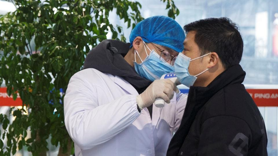 A medical official takes the body temperature of a man at the departure hall of the airport in Changsha, Hunan Province, as the country is hit by an outbreak of a new coronavirus.