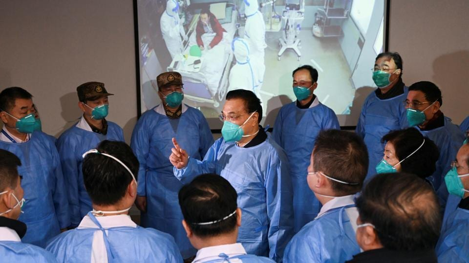 Chinese Premier Li Keqiang wearing a mask and protective suit speaks to medical workers as he visits the Jinyintan hospital where the patients of the new coronavirus are being treated following the outbreak, in Wuhan.