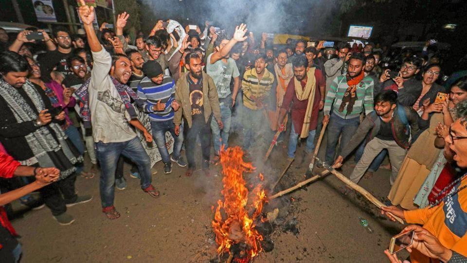 Students of Visva-Bharati University burn an effigy during a protest against.