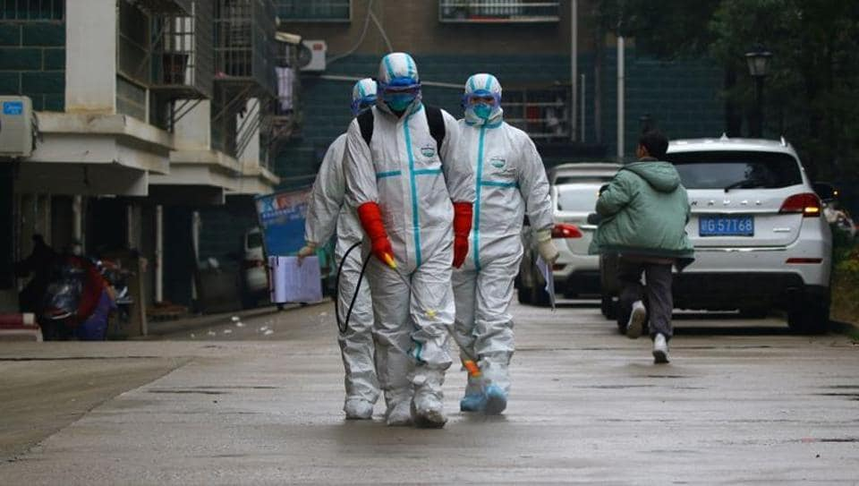 Workers from local disease control and prevention department in protective suits disinfect a residential area following the outbreak of a new coronavirus, in Ruichang, Jiangxi province, China January 25, 2020.