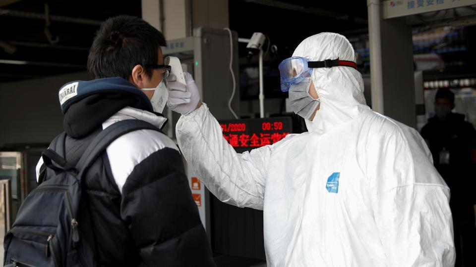 A worker in protective suit uses a thermometer to check the temperature of a man while he enters the Xizhimen subway station, in Beijing, on Monday.