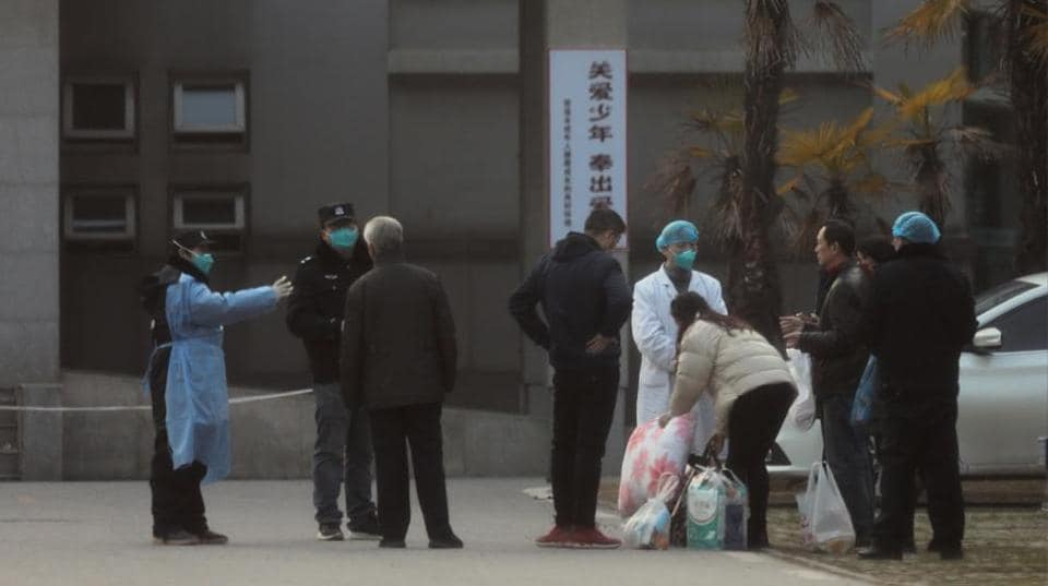 Medical staff and security personnel stop patients' family members from being too close to the Jinyintan hospital, where the patients with pneumonia caused by the new strain of coronavirus are being treated, in Wuhan, Hubei province, China January 20, 2020.