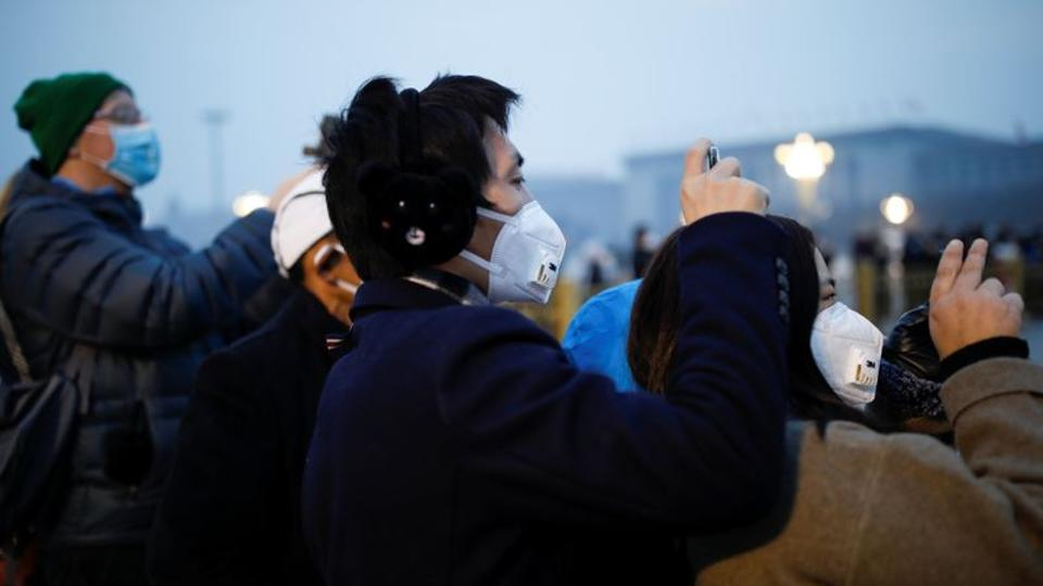 People wearing face masks use their cellphones at the Tiananmen Square, as the country is hit by an outbreak of the new coronavirus, in Beijing, China.