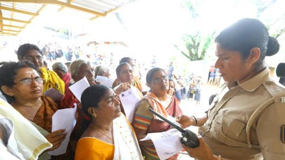 A police personnel checks the age proof of women devotees at the Pamba base camp of Sabarimala Temple