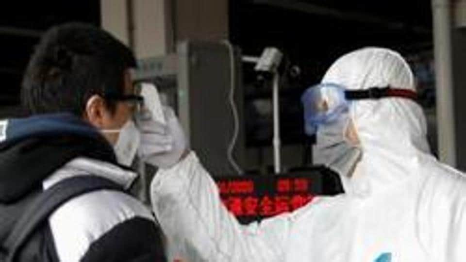 A worker in protective suit uses a thermometer to check the temperature of a man while he enters the Xizhimen subway station in China, as the country is hit by an outbreak of the new coronavirus, in Beijing, China January 27, 2020.