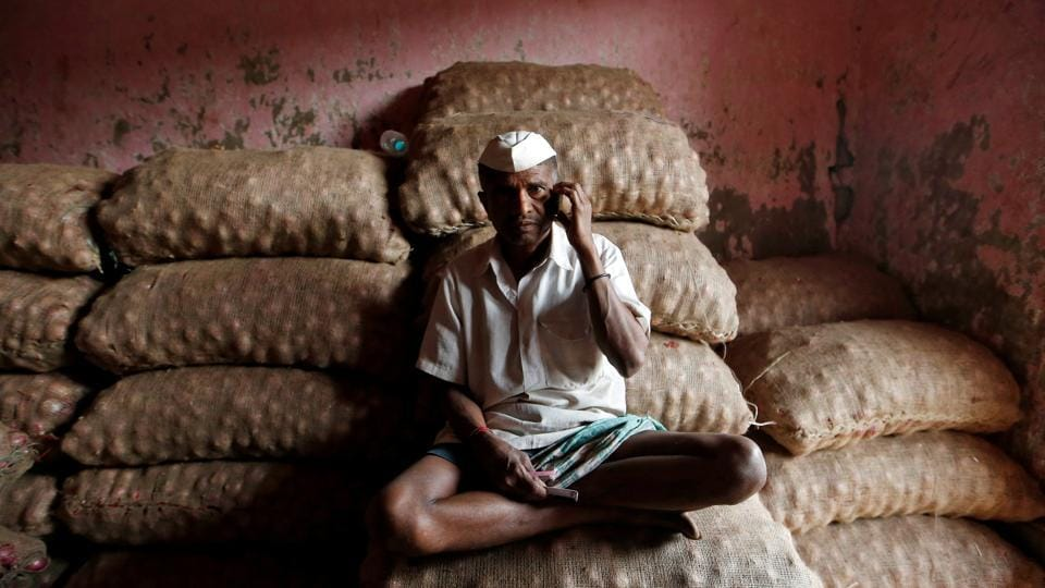 A labourer talks on his mobile phone as he sits on sacks of onions at a wholesale market in Mumbai.