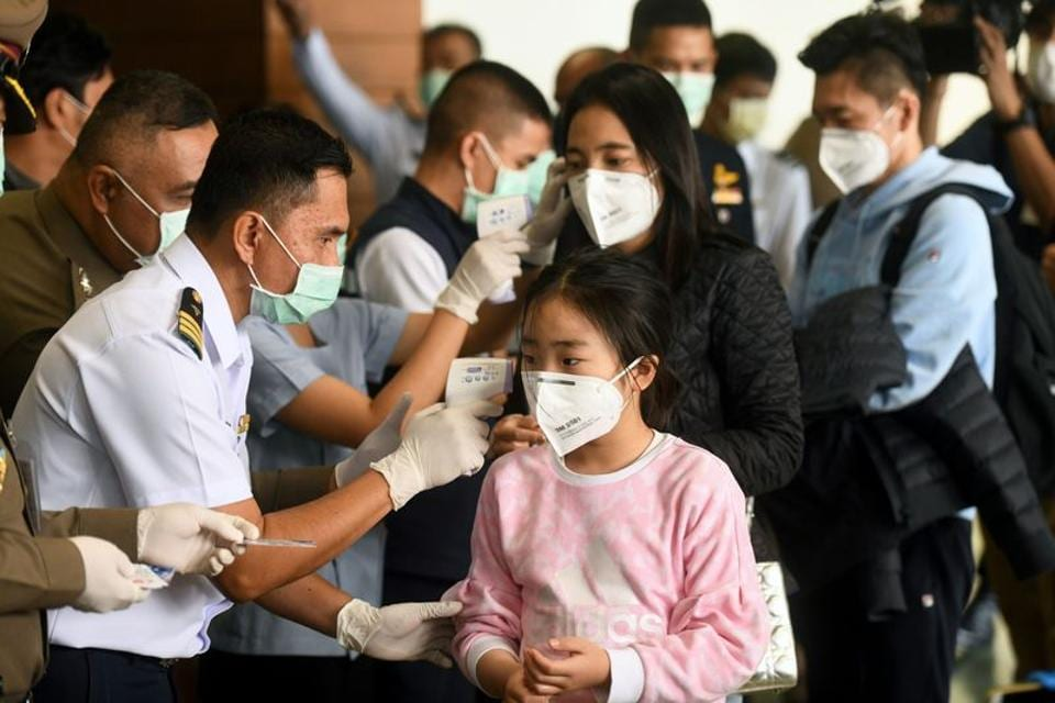 Health workers use infrared thermometers to check the temperature of tourists who arrive at Bangkok's Don Mueang Airport, Thailand, January 25, 2020. Picture taken January 25, 2020. REUTERS/Panumas Sanguanwong NO RESLAES. NO ARCHIVES.
