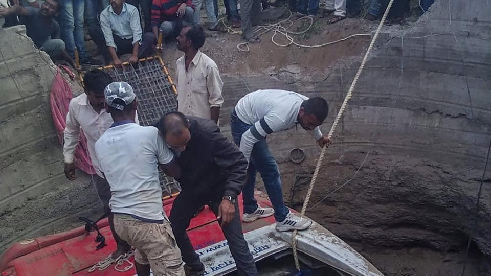 Rescue workers trying to save passengers from a bus which collided with a rickshaw and fell into a well, in Nashik.