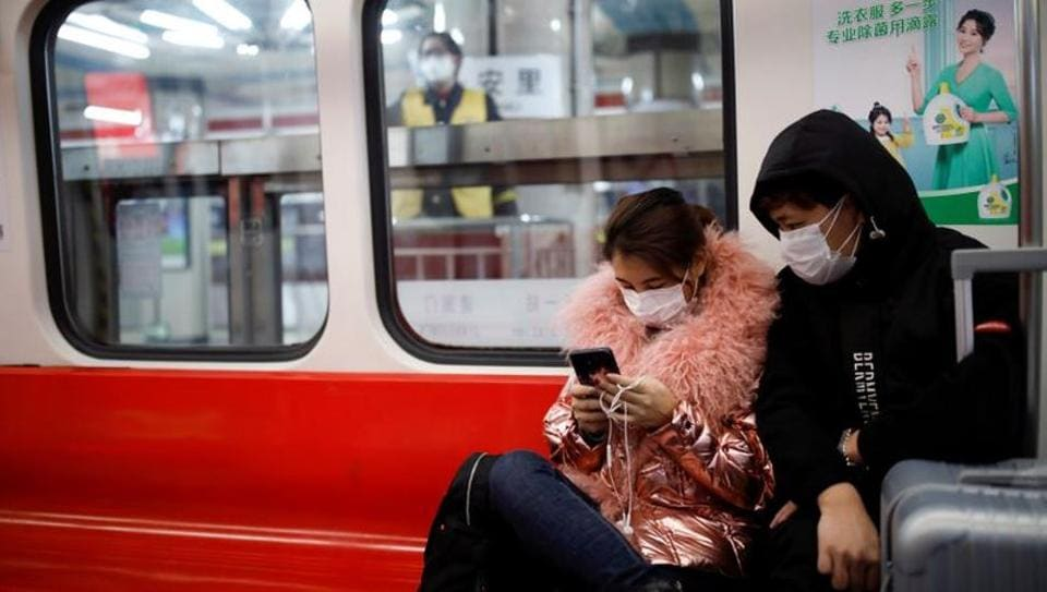 FILE PHOTO: People wearing masks travel in the subway, as the country is hit by an outbreak of the new coronavirus, in Beijing, China January 28, 2020. REUTERS/Carlos Garcia Rawlins