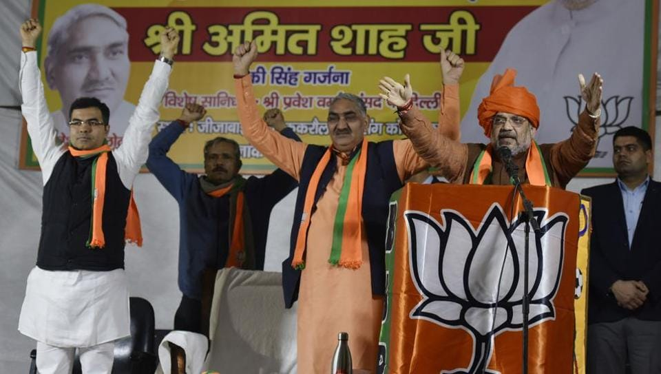 Home Minister Amit Shah addresses the audience during a rally in the presence of party MP Parvesh Verma, at Mahila Park, Matiala.