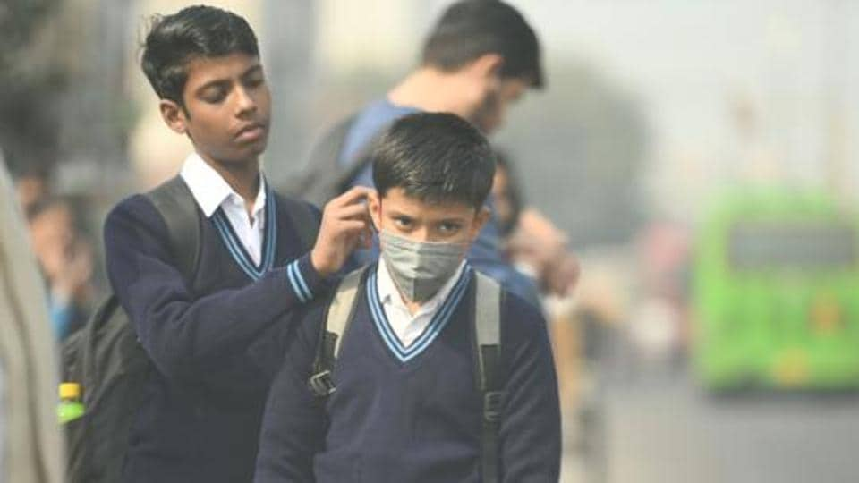 A student helps another with an anti pollution facemask on their way to school, in New Delhi.