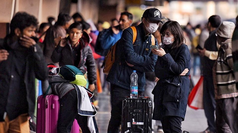 Tourists cover their face with masks in light of novel coronavirus scare as Jaipur health department is on alert, at Jaipur Railway Station.
