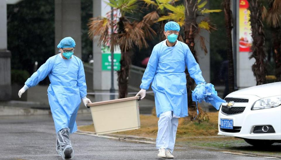 Medical staff carry a box as they walk at the Jinyintan hospital, where the patients with pneumonia caused by the new strain of coronavirus are being treated, in Wuhan, Hubei province, China.