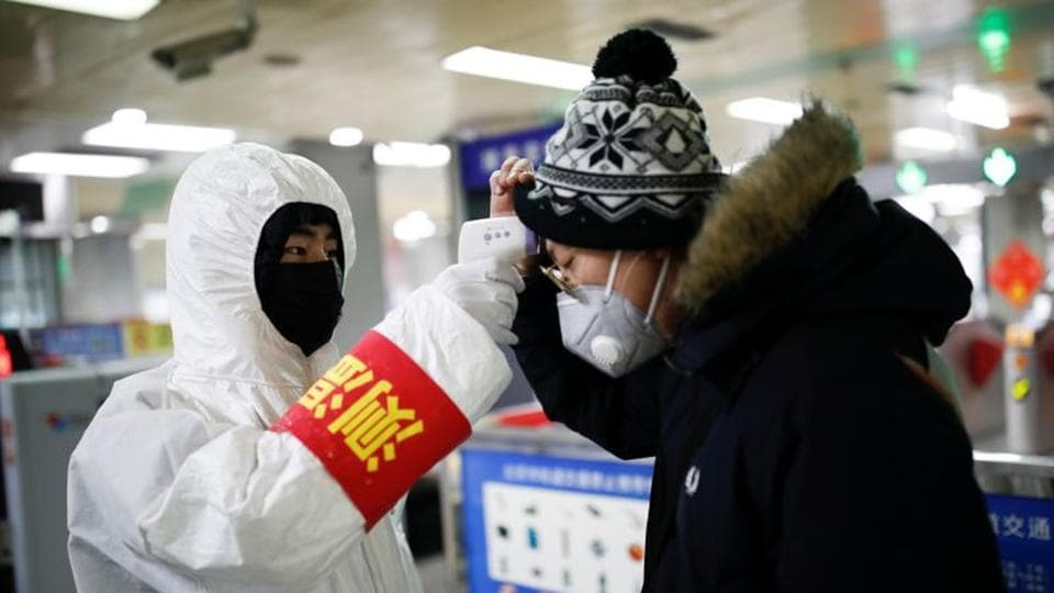 A staff member inBeijing checks the temperature of a passenger entering a subway station, as China is hit by an outbreak of the new coronavirus, on January 28.