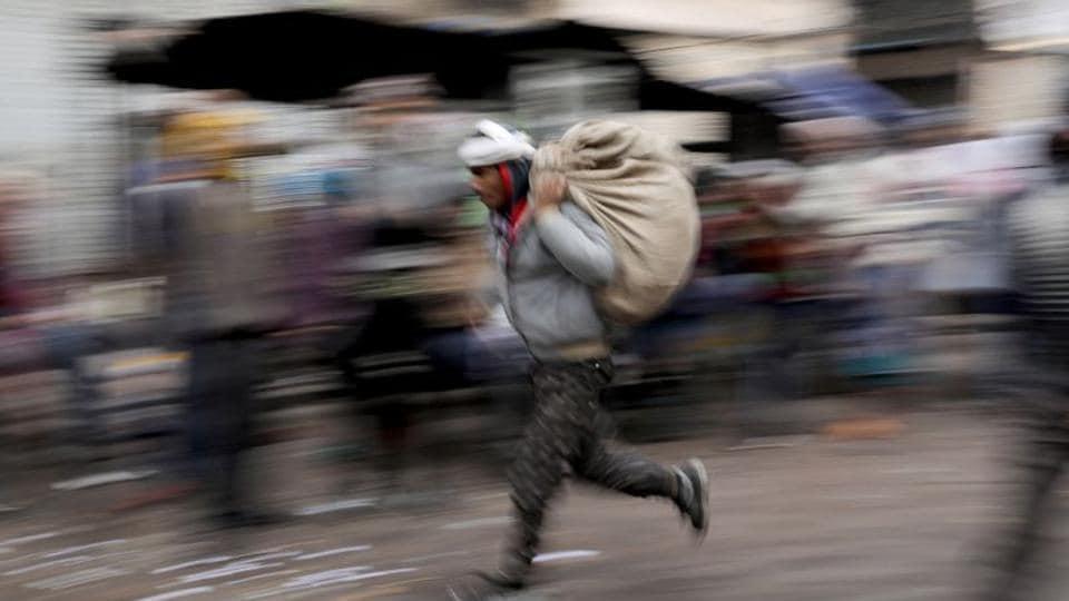A labourer runs across a wholesale market in the old quarters of Delhi.
