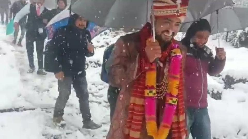 The groom walked with an umbrella through the snow with a big smile on his face.