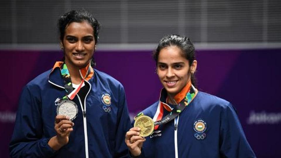 Pusarla V. Sindhu of India (L) and bronze medalist Saina Nehwal of India (R) celebrate on the podium.