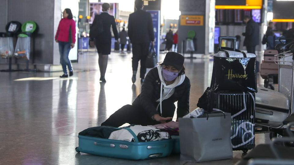 A woman wearing a face mask packs her suitcase in the departures area of Terminal 5, after it was announced British Airways has suspended all services to and from China, at London's Heathrow Airport on Wednesday.