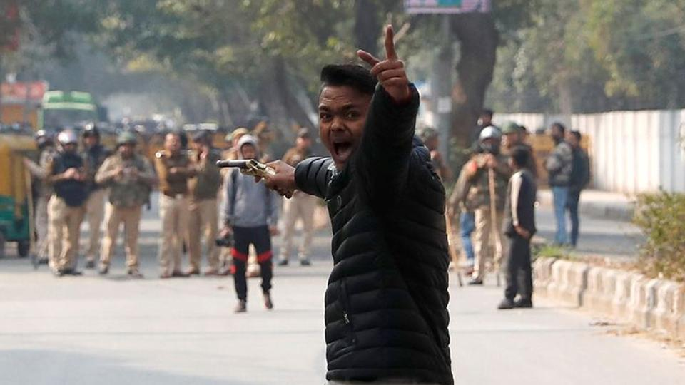 An unidentified man reacts as he brandishes a gun during a protest against amended citizenship law outside the Jamia Millia Islamia university in New Delhi on January 30, 2020.