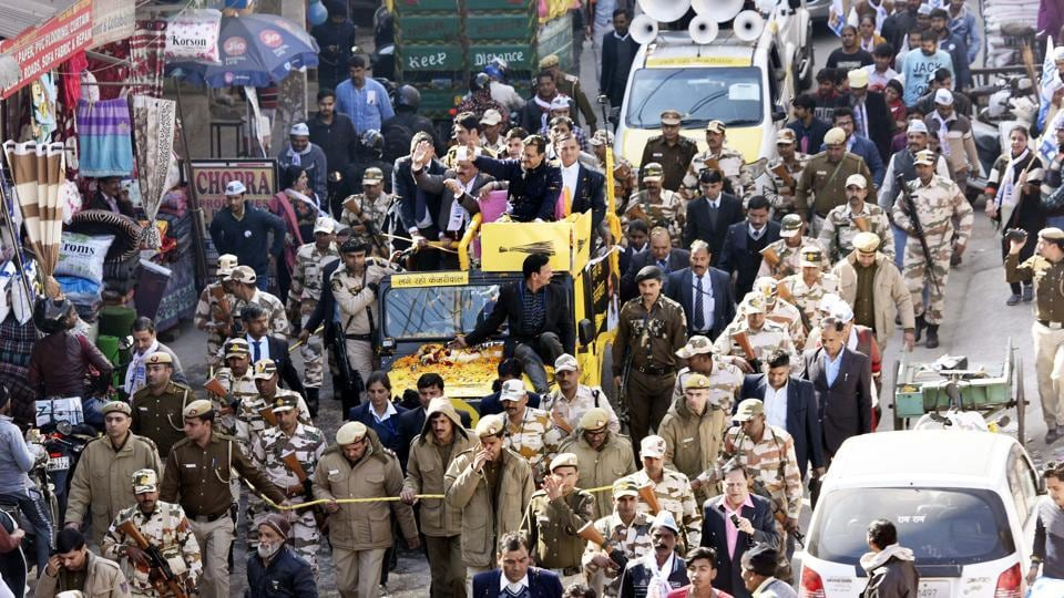 Delhi chief minister Arvind Kejriwal is surrounded by police personnel as he waves during a road show for Janakpuri constituency ahead of the Delhi Vidhan Sabha elections in New Delhi.