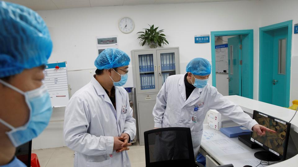 Doctors look at a screen that shows the ward where patients who are infected with the coronavirus are treated at the First People's Hospital in Yueyang, Hunan Province, near the border to Hubei Province, which is under partial lockdown after an outbreak of a new coronavirus, in China.