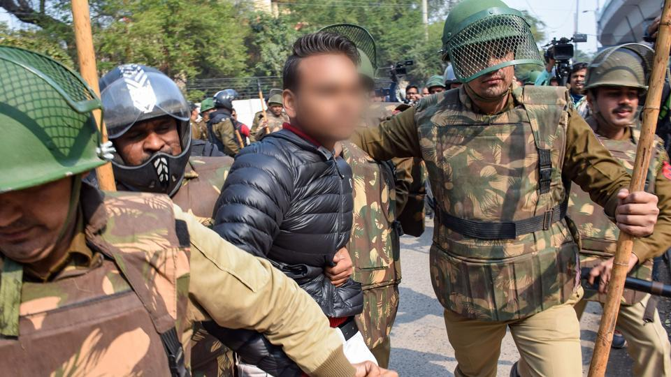 Police detain an unidentified person (face blurred as his being an adult could not be ascertained), after he allegedly brandished a gun and opened fire towards students protesting against the Citizenship Amendment Act, near Jamia Millia Islamia University, in New Delhi.