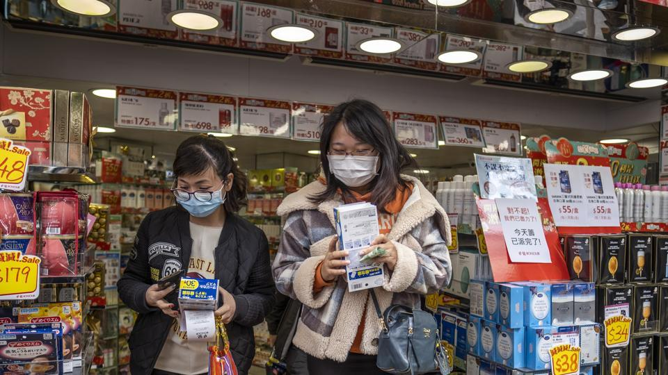 Customers leave with boxes of newly purchased protective masks at a Bonjour Holdings Ltd. store in Hong Kong, China.
