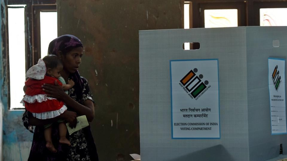 A voter, carrying her son, casts her vote during the repolling at Daryaganj, in Delhi.