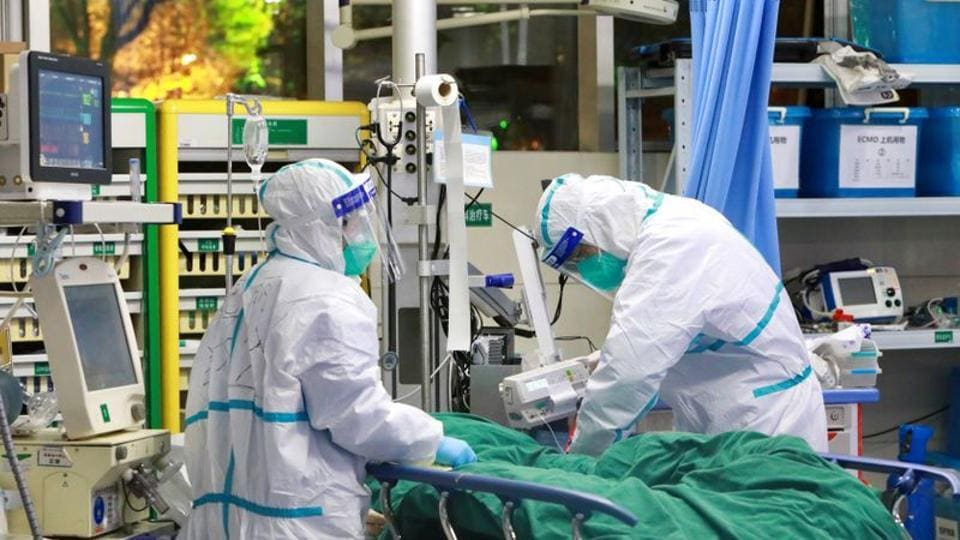 Medical staff in protective suits treat a patient.