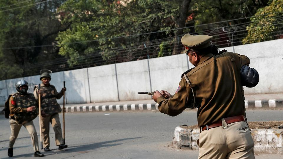 Police officer detains an unidentified man after he shot a student during a protest against a new citizenship law outside the Jamia Millia Islamia university in New Delhi.
