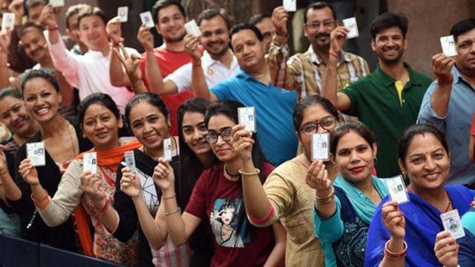 People show voter IDs before casting their vote at RSKV School, West Vinod Nagar.