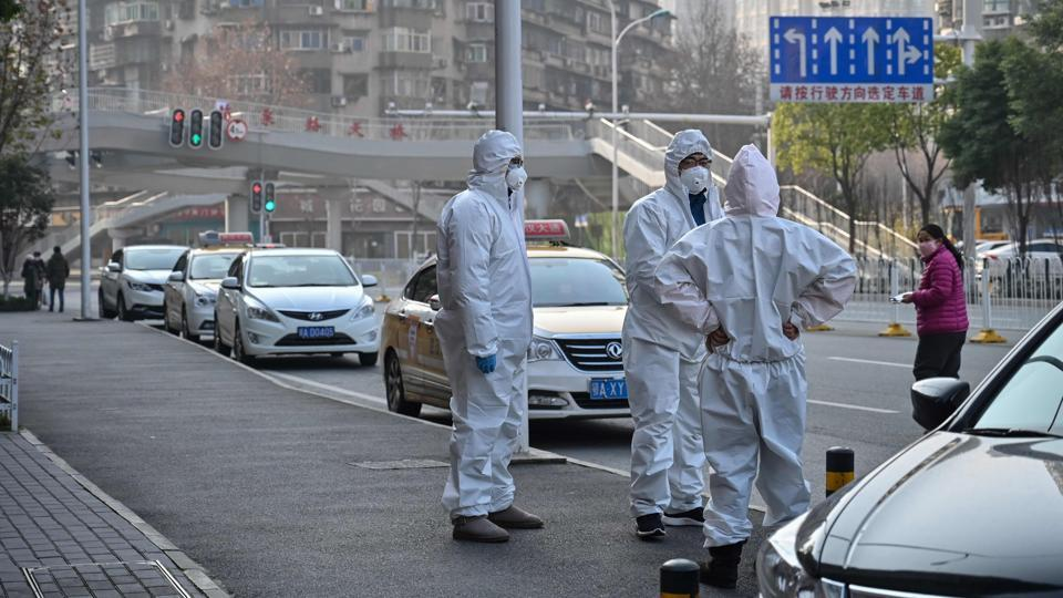 Officials in protective suits gathered on a street in Wuhan.The WHO declared a global emergency over the new coronavirus.