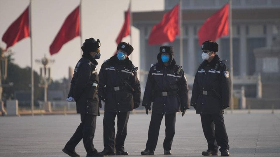 Police officers wearing masks are seen at at the Tiananmen Square, as the country is hit by an epidemic of the new coronavirus, in Beijing, China.