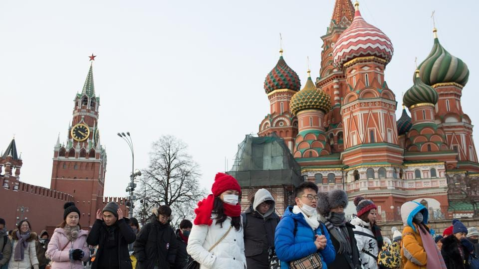 Tourists wear protective face masks as they walk in Red Square near the Kremlin in Moscow.