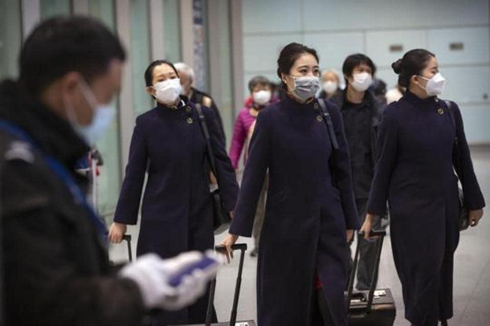 Flight crew members wearing face masks walk through the international arrivals area at Beijing Capital International Airport on January 30.