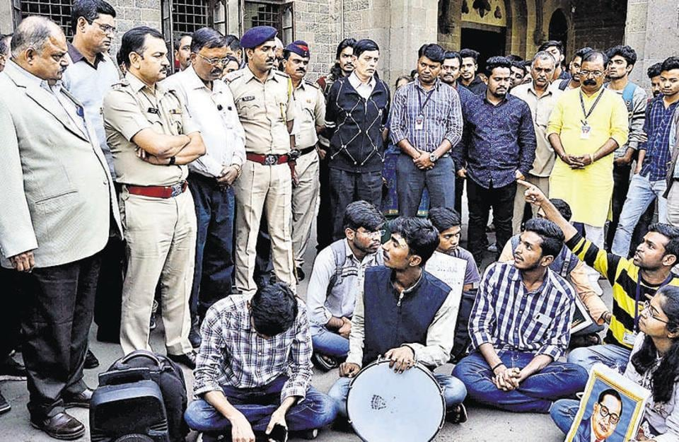 Ravindra Pardeshi (left), principal, Fergusson College and police personnel, attempt to reason with the protesting students.