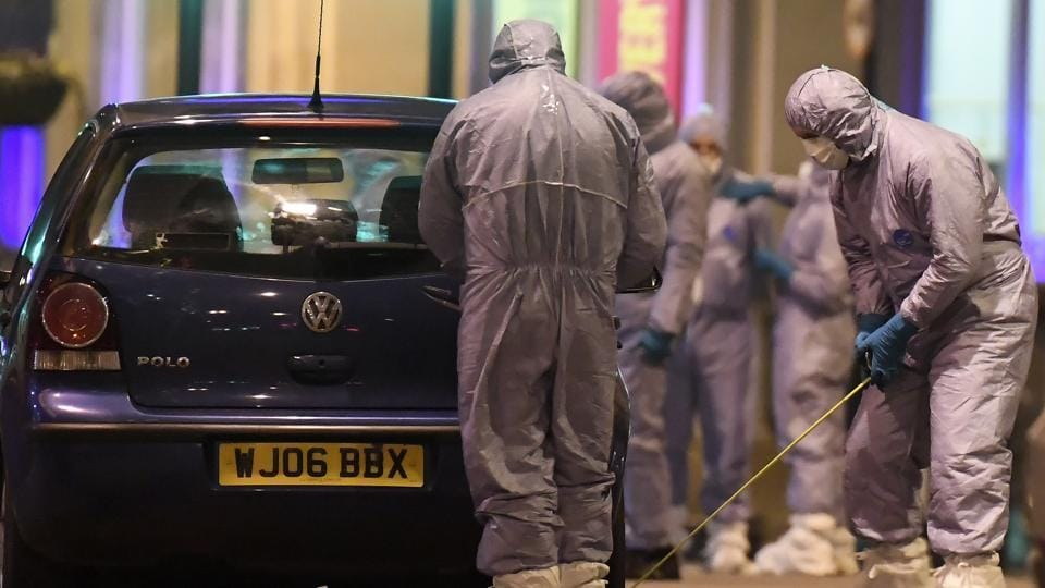 Police forensic officers work near a car at the scene after a stabbing incident in Streatham London, England