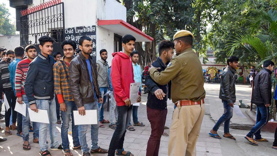 Security personnel frisk examinees before entering the examination hall in Patna on Monday. To prevent cheating, CCTV cameras have been put in place as lakhs of students across Bihar are appearing for the BSEB Board Exam 2020.