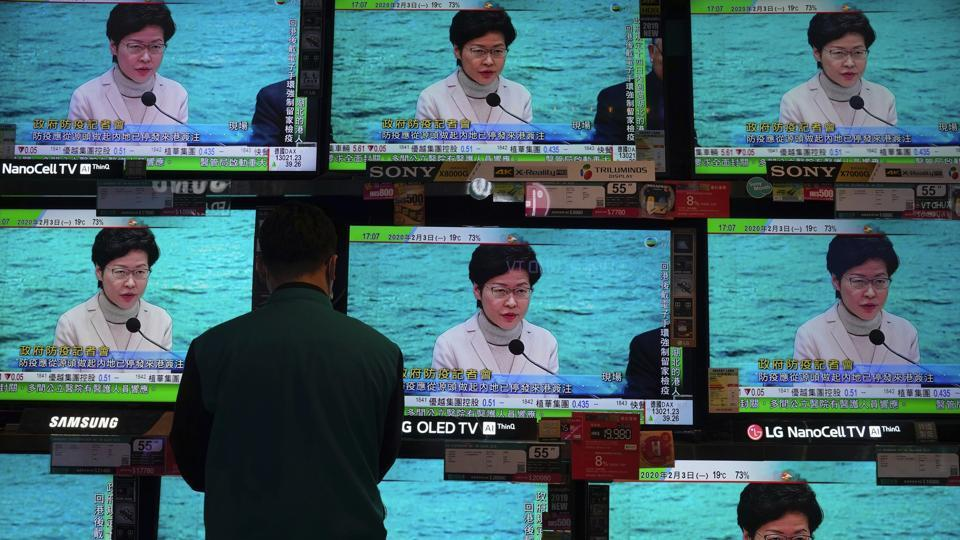 A man wears protective face masks stands in front of TV screens broadcasting Hong Kong Chief Executive Carrie Lam delivering a speech in Hong Kong.