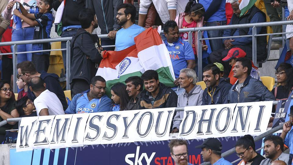 Indian fans sit in front of a sign for former player MS Dhoni during game four of the Twenty20 series between New Zealand and India at Sky Stadium on January 31, 2020 in Wellington, New Zealand.