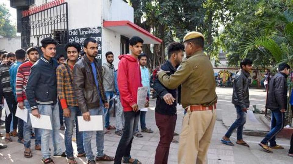 Patna: Security personnel frisk examinees before entering the examination hall, in Patna