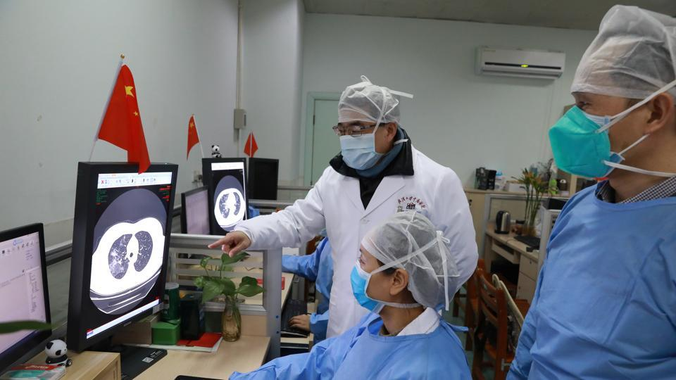 Medical workers inspect the CT (computed tomography) scan image of a patient at the Zhongnan Hospital of Wuhan University following an outbreak of the new coronavirus in Wuhan, Hubei province.