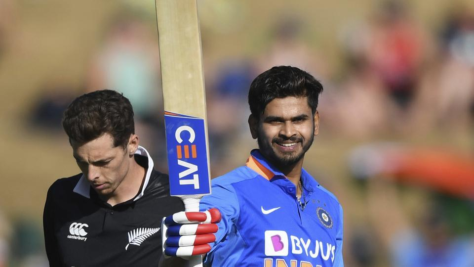 India's Shreyas Iyer celebrates his century - 100 not out as New Zealand's Mitchell Santner looks on.
