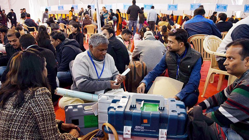Polling officials checking the Electronic Voting Machine (EVMs) and other necessary inputs required for the Delhi Assembly Election, at a distribution centre, at Kamla Nehru College, in New Delhi on Friday. (ANI PHOTO)