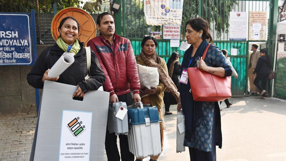 Electoral officials carry Electronic Voting Machines (EVM) and Voter Verifiable Paper Audit Trail (VVPAT) while heading towards their respective centre ahead of Delhi Vidhan Sabha elections