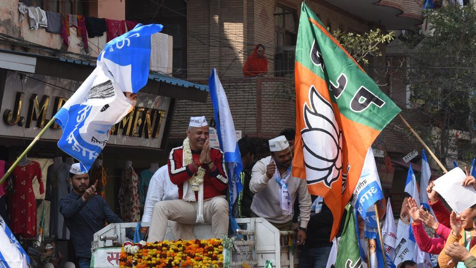 A BJP rally runs into Delhi Deputy CM and AAP candidate from Patparganj constituency Manish Sisodia while on an election campaign roadshow at Sabzi Mandi in New Delhi. (Sonu Mehta / HT Photo)