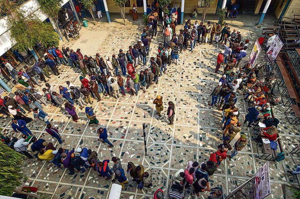 People wait in queues to cast their votes at Shaheen Public School polling station in the Shaheen Bagh area, which has been witnessing a peaceful protest against the Citizenship Act for several weeks, during the Delhi Assembly elections, in New Delhi, Saturday, Feb. 8, 2020.