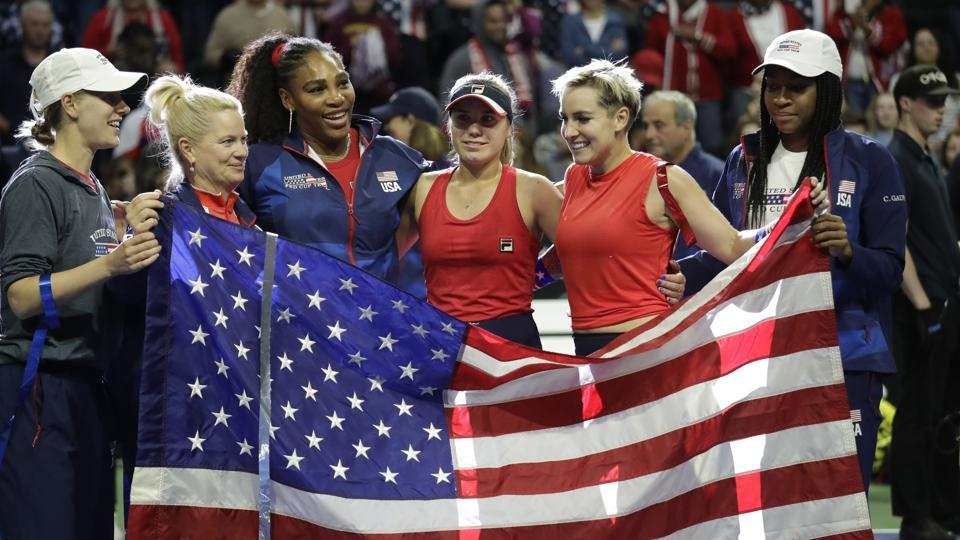 The United States Fed Cup team of Alison Riske, left, captain Kathy Rinaldi, Serena Williams, Sofia Kenin Bethanie Mattek-Sands and Coco Gauff pose with an American flag after beating Latvia in Fed Cup.