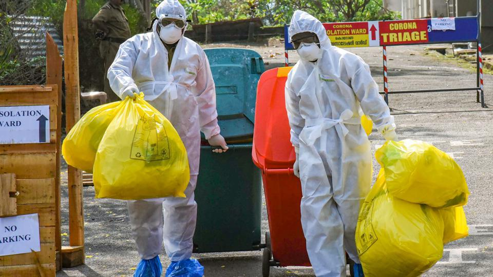 Medical staff, wearing protective suits, hold medical waste as they exit the Special Isolation Ward set up to provide treatment to novel coronavirus patients at Kochi Medical college, in Kerala, Saturday, Feb. 8, 2020.
