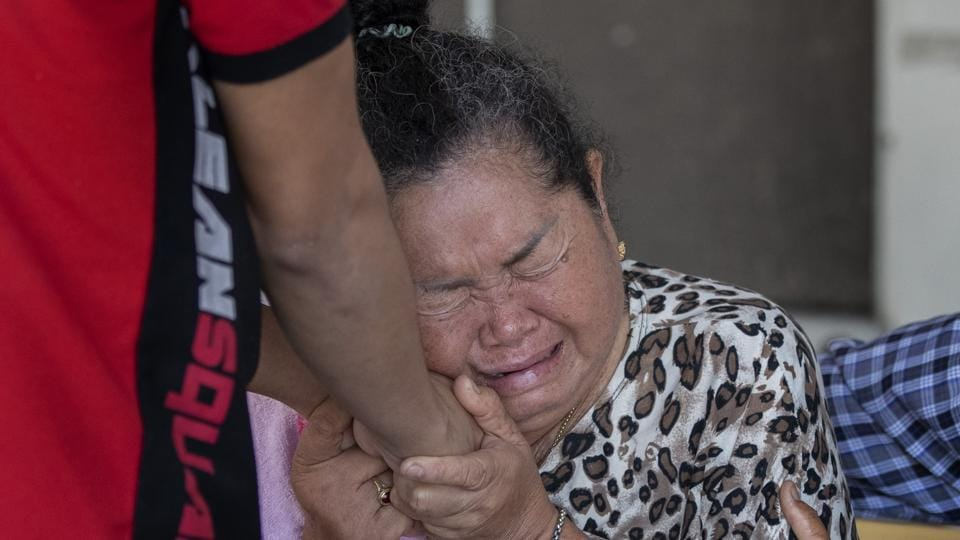 People comfort the relative of a victim in the mass shooting in Korat, Nakhon Ratchasima, Thailand, Sunday, Feb. 9, 2020.